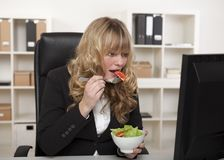 Businesswoman having a quick snack at her desk Royalty Free Stock Photo