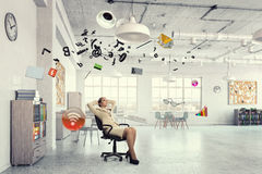 Businesswoman having rest in office . Mixed media Royalty Free Stock Images