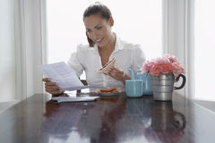 Businesswoman Having Sandwich While Reading Document At Home Stock Images