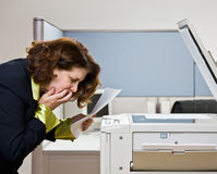 Businesswoman having trouble with copy machine Stock Image