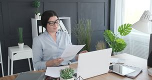 Businesswoman having video conference using office laptop. Businesswoman using documents while having video conference on office laptop stock video footage