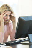 Businesswoman With Head In Hands Looking At Computer Stock Image