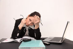 Businesswoman headache. Tired businesswoman is sitting behind her laptop with headache Royalty Free Stock Photos