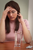 Businesswoman with headache take pill at office Stock Images