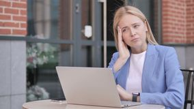 Businesswoman with headache using laptop, sitting outdoor. 4k high quality, 4k high quality stock video