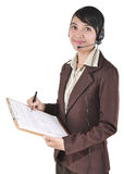 Businesswoman with headphone making notes Stock Photo