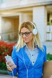 Businesswoman with headphones looking mobile. Businesswoman with headphones looking at the mobile in the street Royalty Free Stock Images