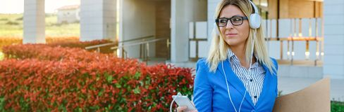 Businesswoman with headphones and mobile. In the street Royalty Free Stock Image