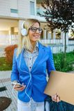 Businesswoman with headphones and mobile. In the street Royalty Free Stock Images