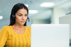 Businesswoman in headphones using laptop Stock Image