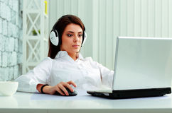 Businesswoman in headphones working on a laptop Royalty Free Stock Image