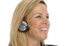 Businesswoman with headset. Businesswoman uses a headset and smiles against a white background Stock Image
