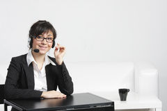 Businesswoman with headset at empty desk Stock Photography