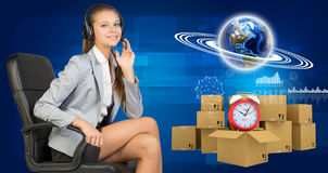 Businesswoman in headset, Globe, commodity boxes Royalty Free Stock Photos