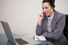 Businesswoman with headset on her laptop Royalty Free Stock Photos