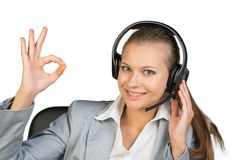 Businesswoman in headset making okay gesture Royalty Free Stock Photography