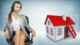 Businesswoman in headset, model house with tag for Royalty Free Stock Image