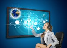 Businesswoman in headset pressing touch screen. Button on virtual interface with Globe and honeycomb shaped icons, on blue background. Element of this image Royalty Free Stock Photography