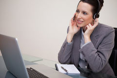 Businesswoman with headset sitting at her desk Stock Photos