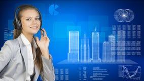 Businesswoman in headset. Skyscrapers beside, hi Stock Photo