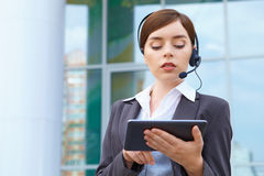 Businesswoman with headset and tablet pc. Royalty Free Stock Images