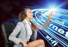 Businesswoman in headset touching or pressing. Businesswoman in headset sitting on office chair, touching spot of light with rays around, smiling. Beside is Stock Image