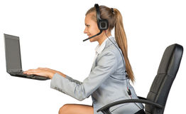 Businesswoman in headset, typing on laptop Stock Photo