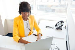 Businesswoman in headset using laptop computer Stock Images