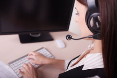 Businesswoman with headset working on computer Stock Images