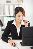 businesswoman with headset working in office Stock Image