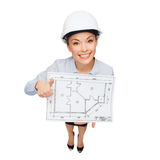 Businesswoman in helmet with blueprint Royalty Free Stock Image