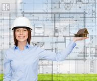 Businesswoman in helmet holding house on palm Royalty Free Stock Image