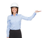 Businesswoman in helmet holding something on palm Royalty Free Stock Photos