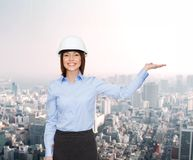 Businesswoman in helmet holding something on palm Royalty Free Stock Photography
