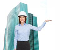 Businesswoman in helmet holding something on palm Stock Photo