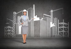 Businesswoman in helmet showing construction site Royalty Free Stock Photos