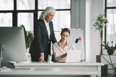 Businesswoman and her boss working with laptop computer in office Stock Image