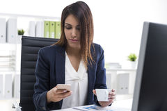 Businesswoman with her cell phone and a cup of coffee Royalty Free Stock Images