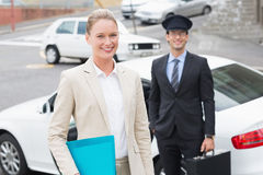 Businesswoman and her chauffeur smiling at camera Royalty Free Stock Images