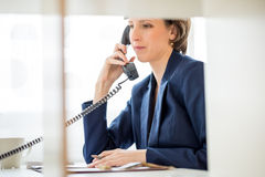 Businesswoman at her Desk Answering a Phone Call Stock Photo