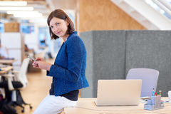 Businesswoman at her desk in open office typing on phone Royalty Free Stock Photography