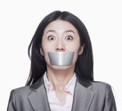 Businesswoman with her mouth caver with duct tape Stock Photos