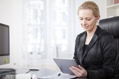 Businesswoman at her Office Using Tablet Computer Royalty Free Stock Photos