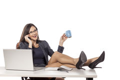 Businesswoman in her office. Young businesswoman with legs on the table talking on the phone, holding a cup and smiling royalty free stock image