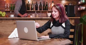 Businesswoman in her 40s opens a laptop and starts working on it. In vintage stylish coffee shop or pub. She puts glasses on while a bartender is working in the stock video footage