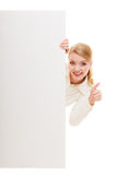 Businesswoman hiding behind blank copy space banner. Advertisement. Woman hiding behind blank copy space banner showing thumb up isolated. Businesswoman Stock Photography