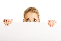 Businesswoman hiding behind an empty billboard Royalty Free Stock Image
