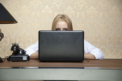 Businesswoman hiding behind a laptop Royalty Free Stock Photography