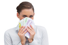 Businesswoman hiding behind money in her hands Stock Image