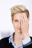 Businesswoman Hiding Eye With Hand In Office Stock Photos
